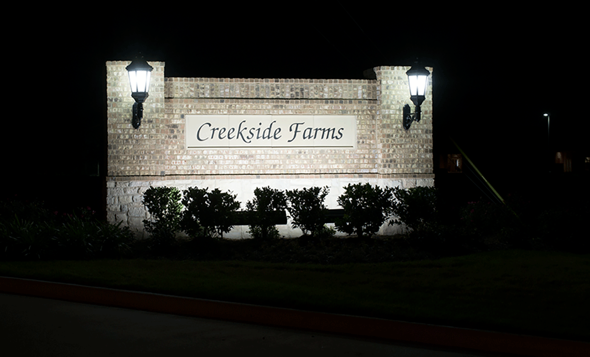 Natural Concepts light fixtures illuminating stone Creekside Farms sign