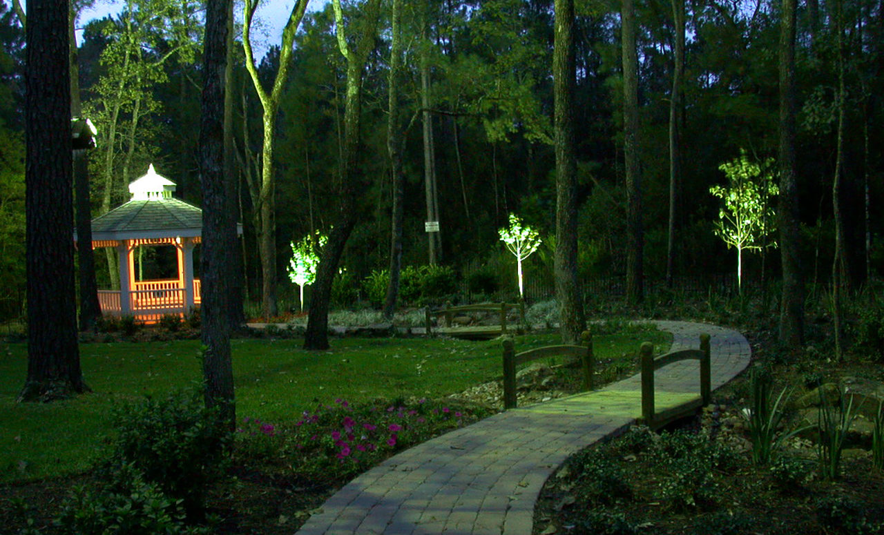 Natural Concepts light fixtures lighting tiny trees along a walkway leading to a warmly lit gazebo