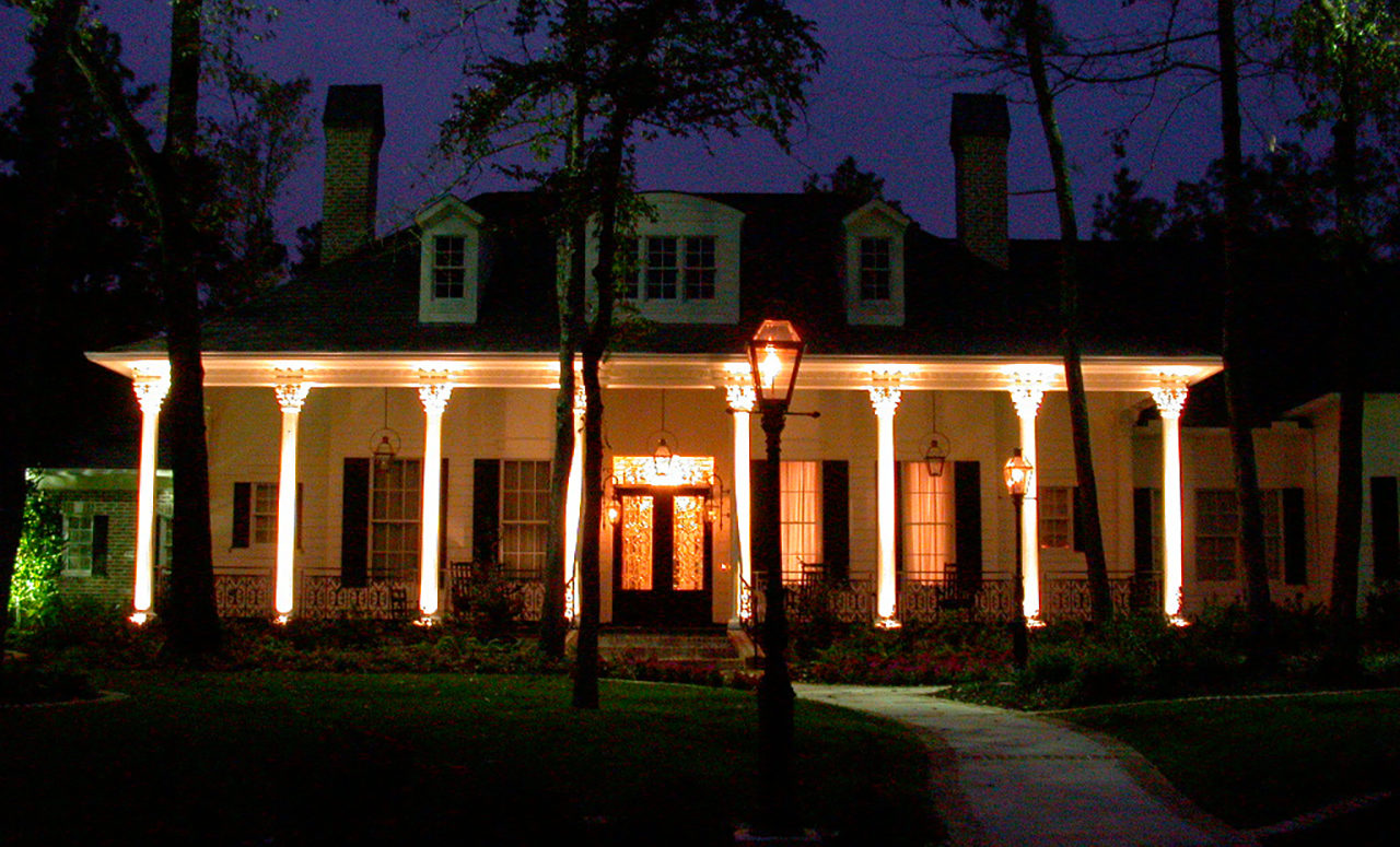 Natural Concepts light fixtures illuminating eight large white columns on the porch of a house