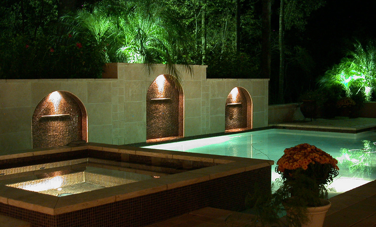 Natural Concepts light fixtures shining downward on a decorative tile wall behind a pool that is illuminated with white lights.