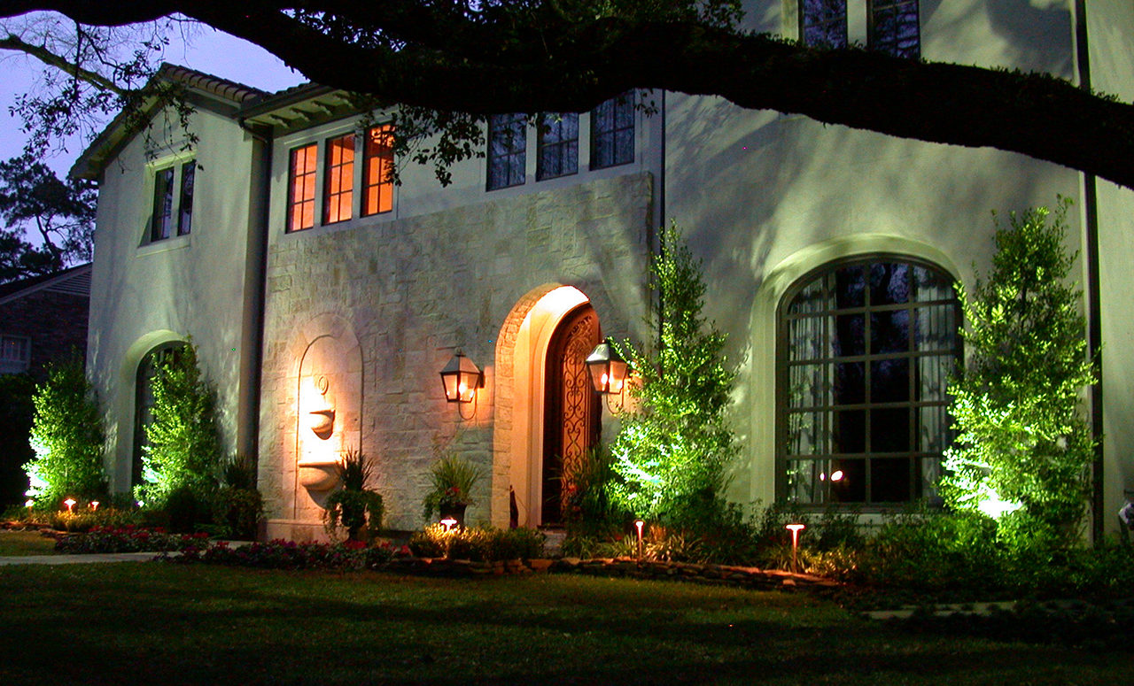 Natural Concepts light fixtures lighting the fountain, trees, and flower beds in the front of a stone house