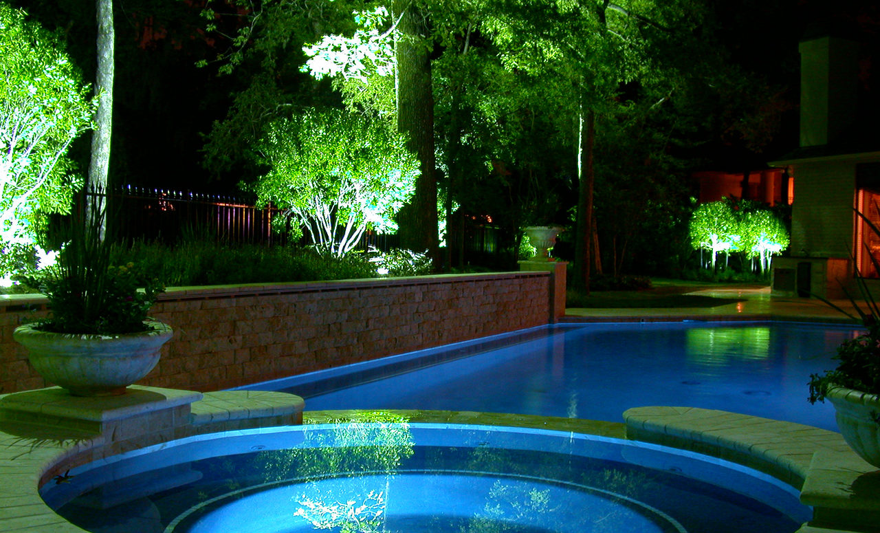 Natural Concepts light fixtures illuminating large pine trees surrounding a blue lighted pool