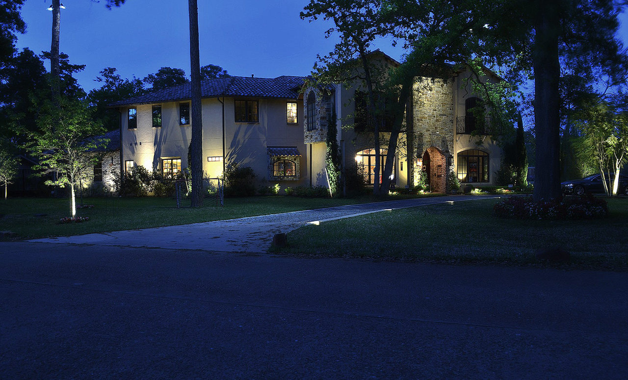 A large stone house with trees surrounding it with soft white lights going up the driveway and bright lanterns lighting the permitter of the house