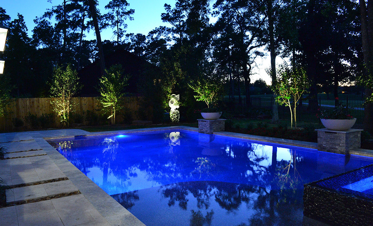 A deep blue pool with the sapling trees around it lighted with soft white lights