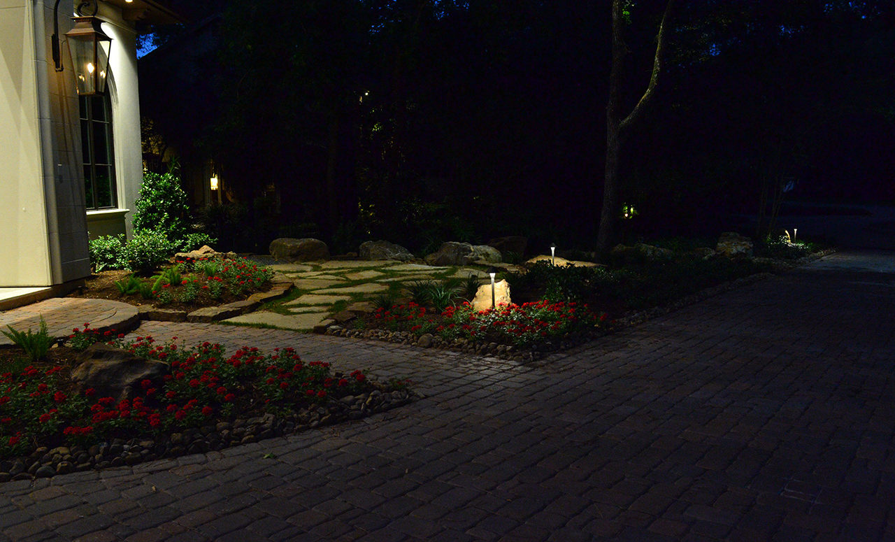 flowerbeds in the front of a house with small lamps