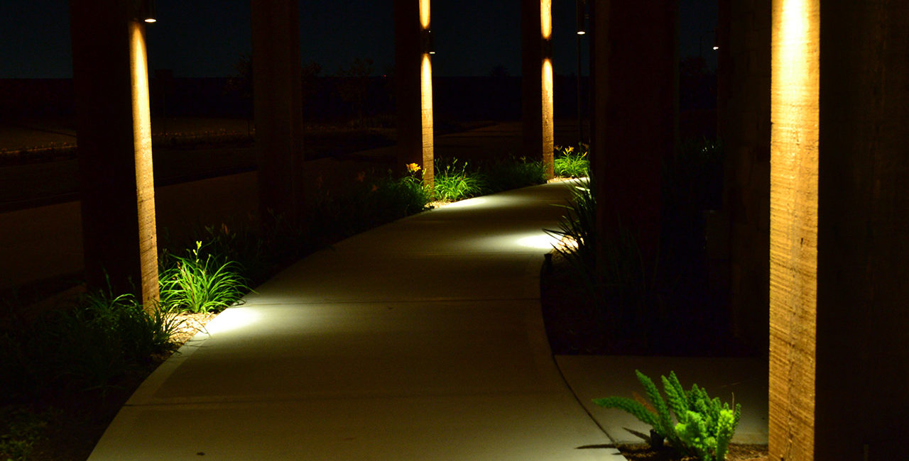 a sidewalk with pillars with lamps shining light up and down the columns.