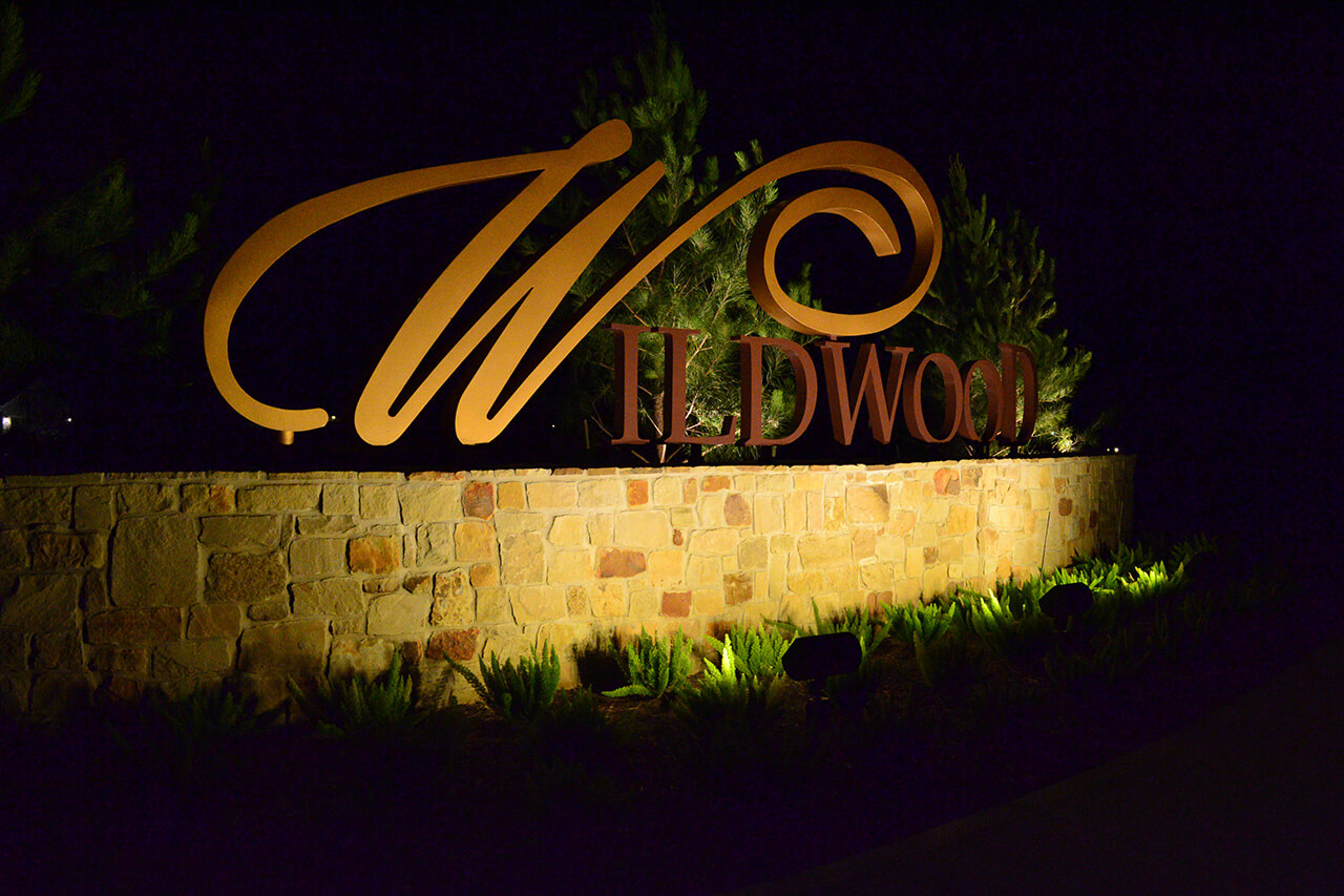 Large metal letters spelling Wildwood fitted on top of a brick wall being lighted by the lamps in the bushes below