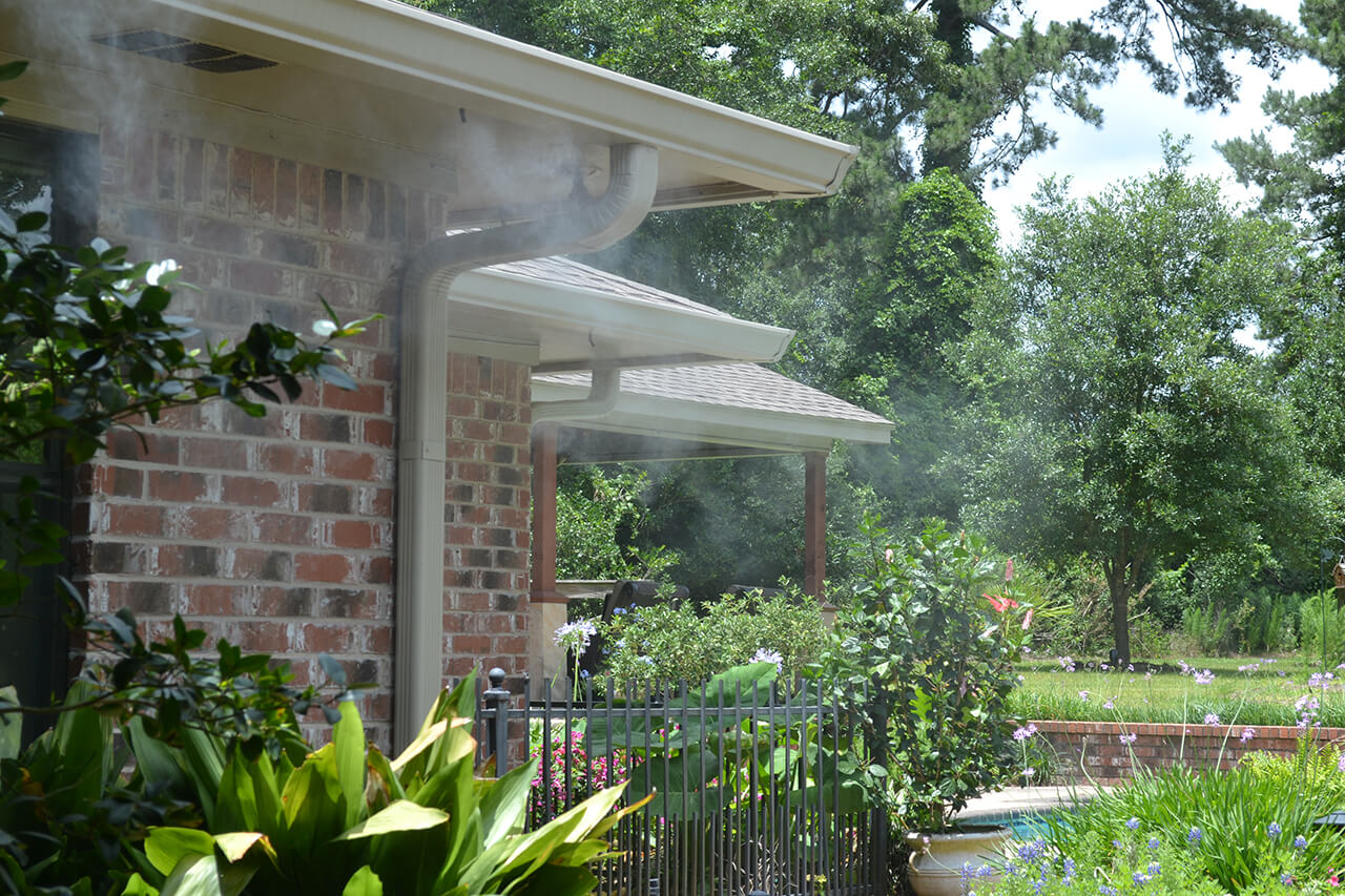 Three nozzles on the edge of the roof of a house spraying mosquito mist in the backyard