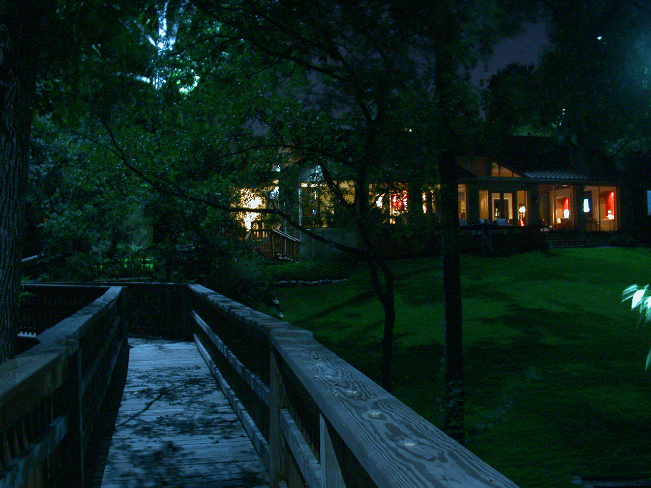 View of the back of a house from a bridge in the backyard being delicately lighted with moonlights in the trees