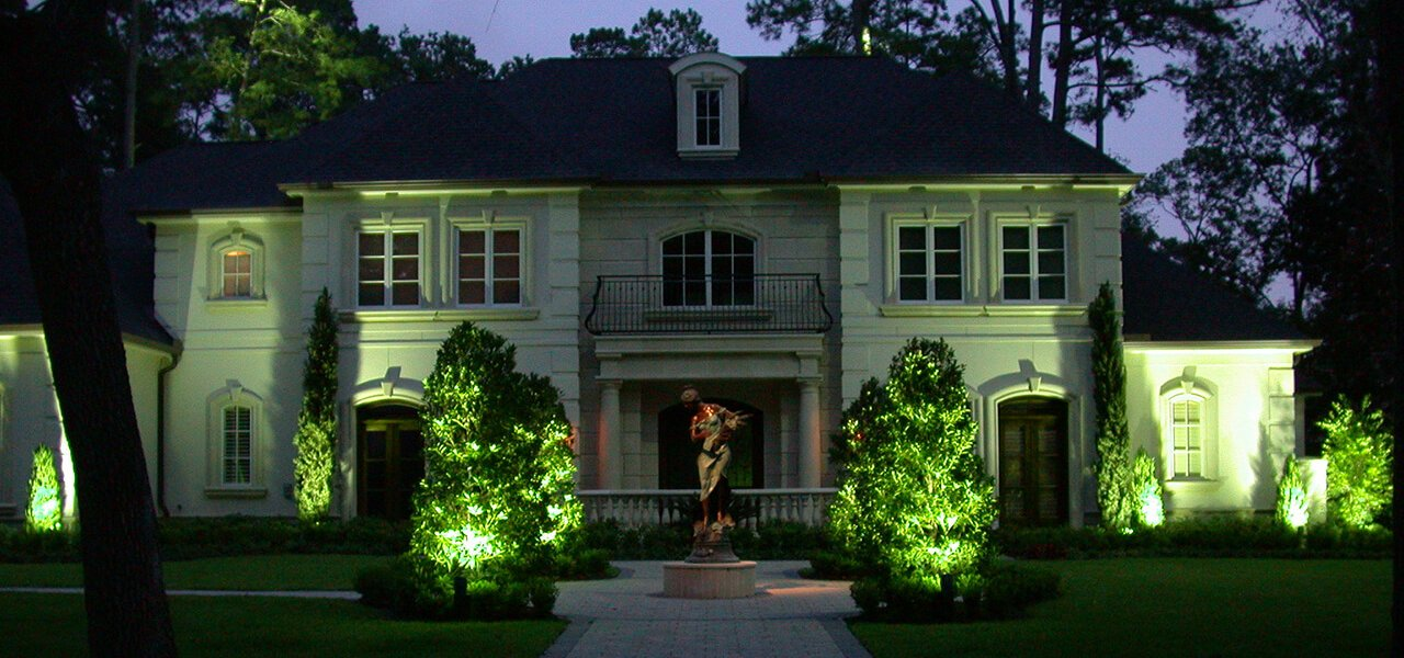 Natural Concepts light fixtures illuminating bushy trees in the front of a house with a statue in the middle