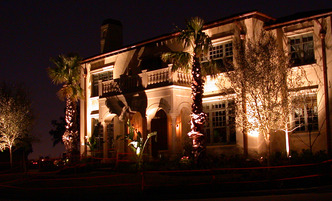 A large house with lights shining on the four trees in the front