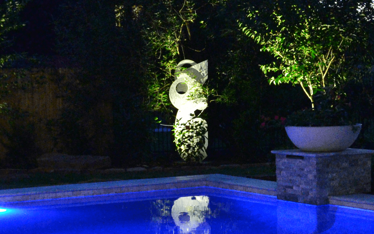 A statue by a pool being lighted with a white light